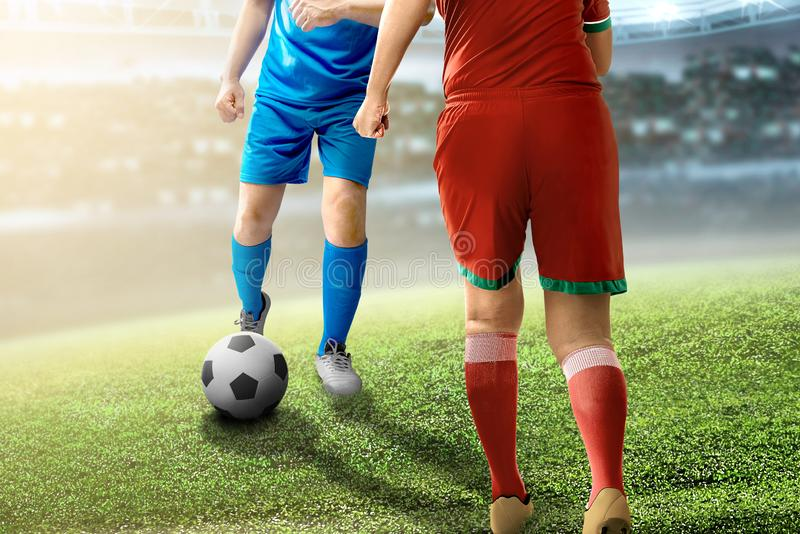 Football player man dribbling the ball trying to past his opponent. On football field at stadium stock image