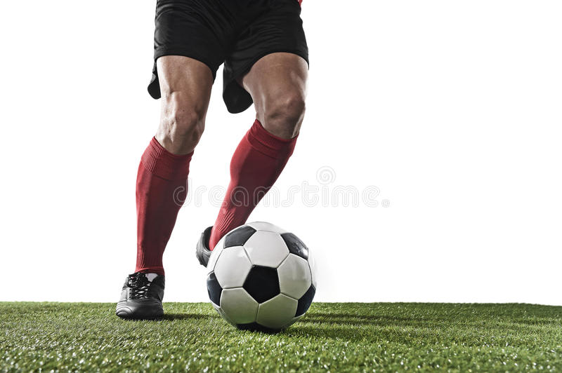 Football player in red socks and black shoes running and dribbling with the ball playing on grass. Close up legs and feet of football player in red socks and stock images