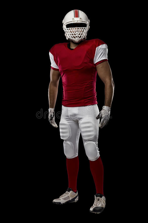 Football Player. With a red uniform on a black background stock photos
