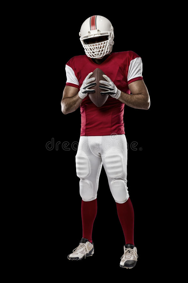 Football Player. With a red uniform on a black background stock image