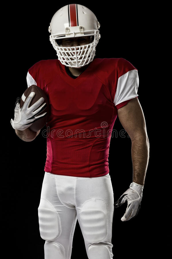 Football Player. With a red uniform on a black background royalty free stock image