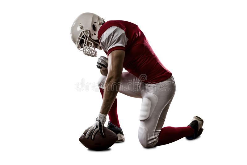 Football Player. With a red uniform on his knees, on a white background royalty free stock photos