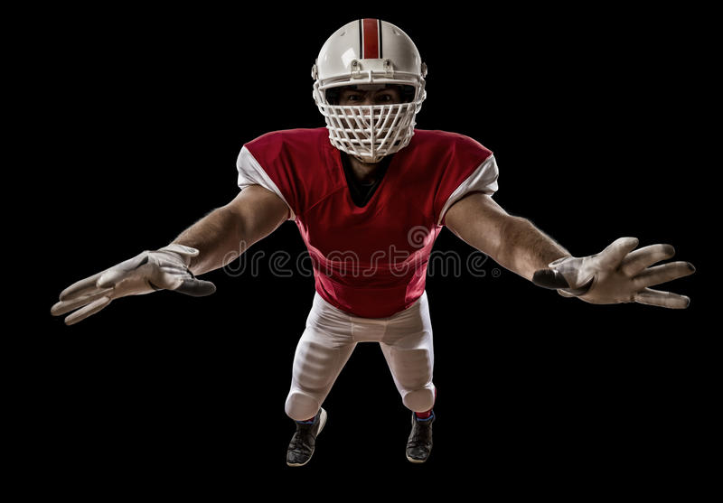 Football Player. With a red uniform making a tackle on a Black background royalty free stock images