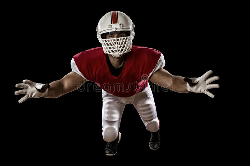 Football Player. With a red uniform making a tackle on a Black background royalty free stock image