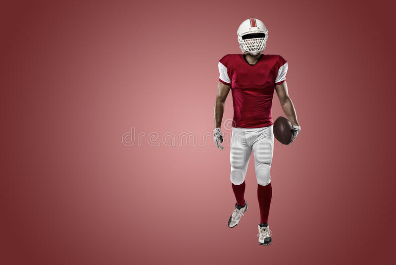 Football Player. With a red uniform on a Red background stock photos