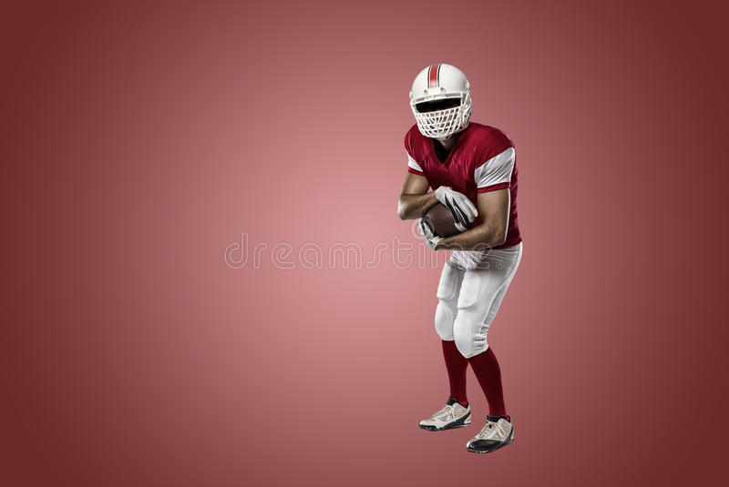 Football Player. With a red uniform on a Red background royalty free stock photo