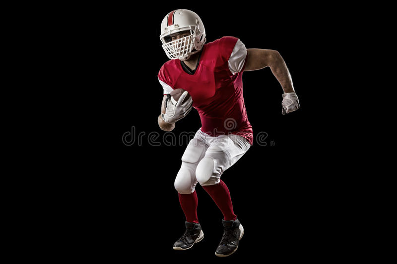Football Player. With a red uniform Running on a Black background royalty free stock photo