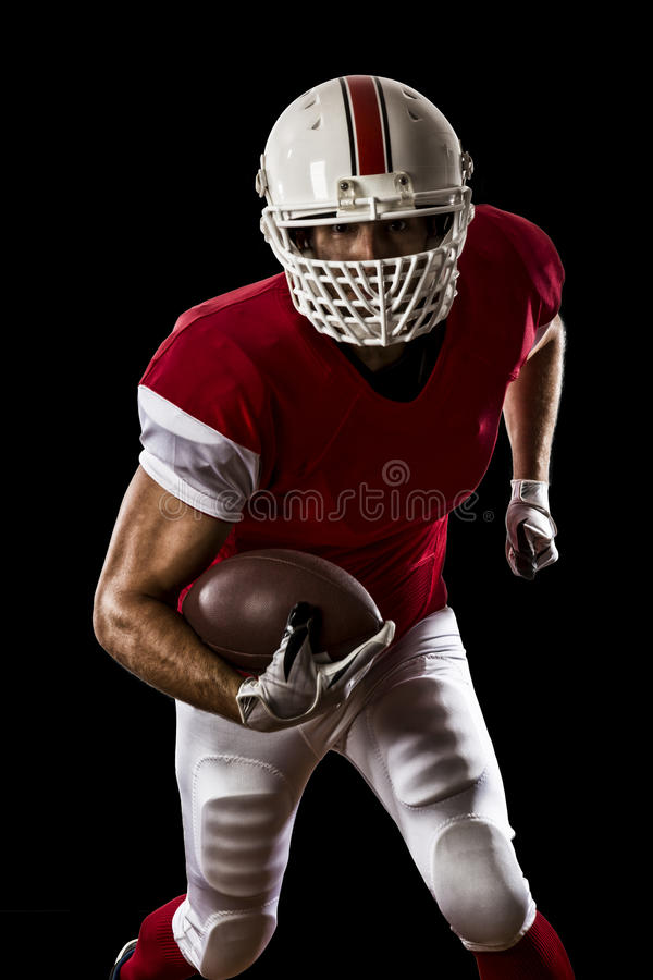 Football Player. With a red uniform Running on a Black background stock photography