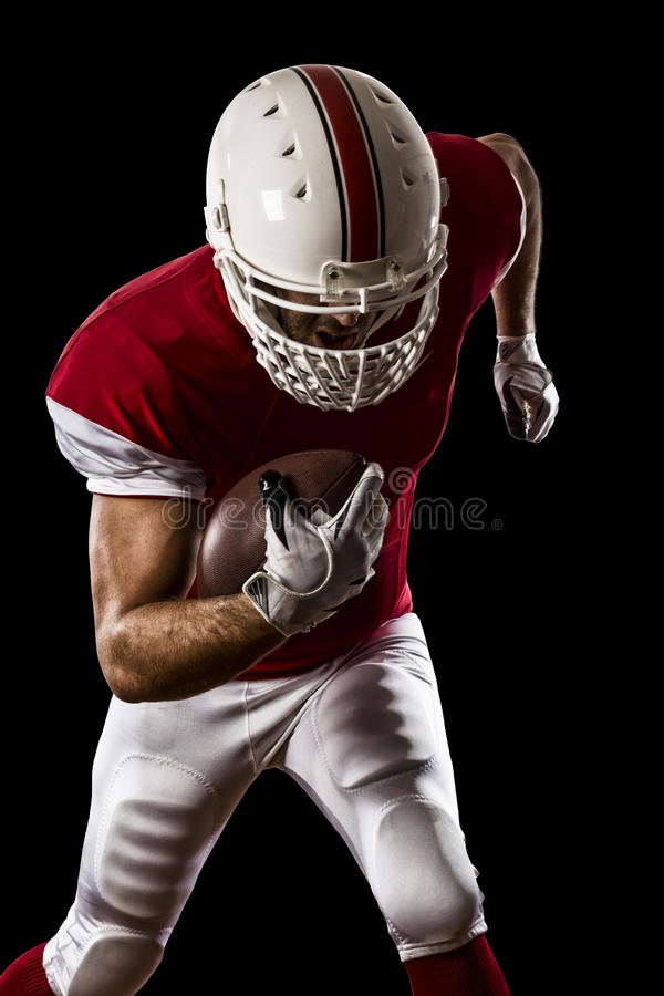 Football Player. With a red uniform Running on a Black background stock photos