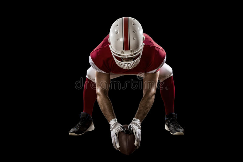 Football Player. With a red uniform on the scrimmage line, on a Black background royalty free stock photography