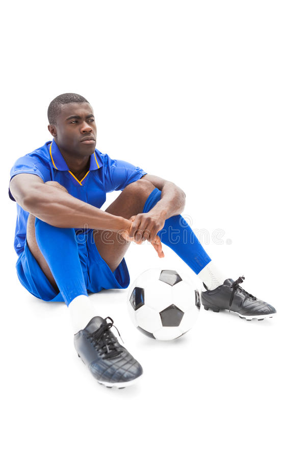 Football player sitting on the ground holding ball. On white background royalty free stock photo