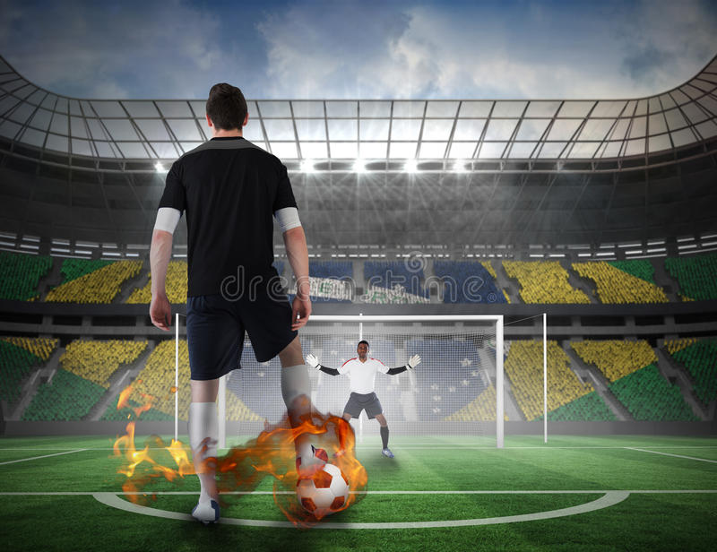 Football player about to take a penalty. Composite image of football player about to take a penalty against football pitch in large stadium royalty free stock photo