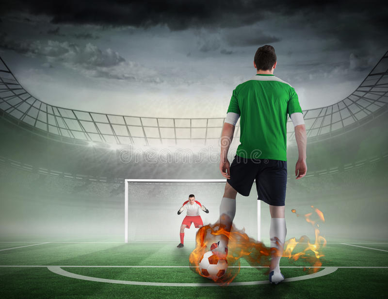 Football player about to take a penalty. Composite image of football player about to take a penalty against football pitch in large stadium stock photos