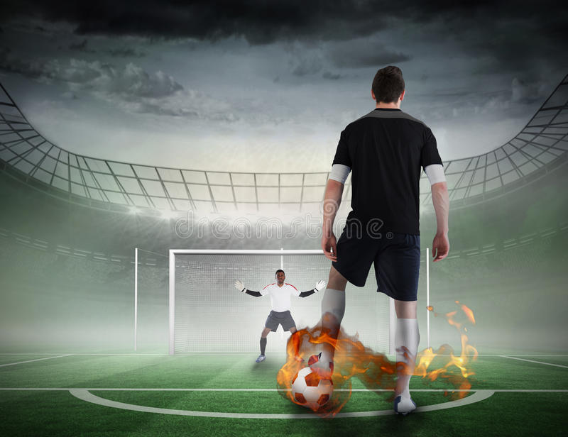 Football player about to take a penalty. Composite image of football player about to take a penalty against football pitch in large stadium stock photography