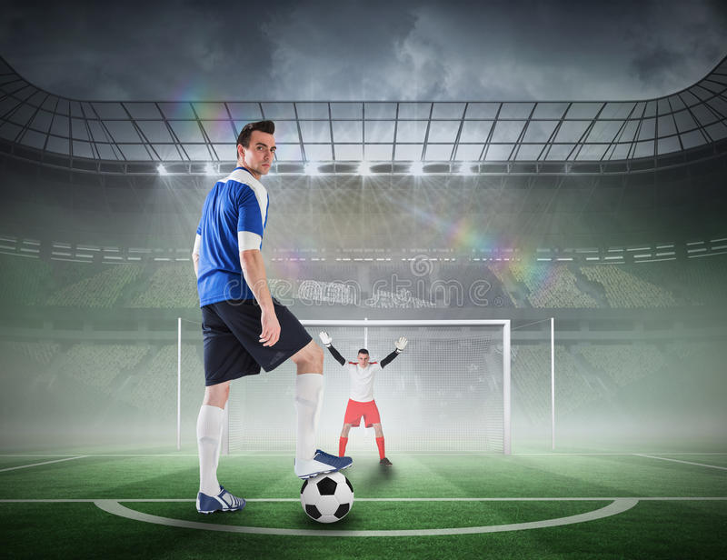 Football player about to take a penalty. Composite image of football player about to take a penalty against football pitch in large stadium royalty free stock image