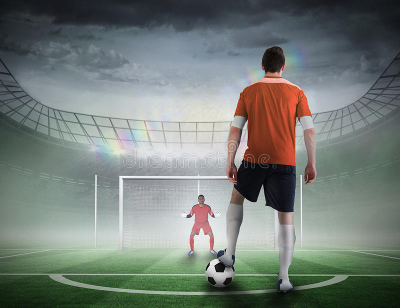Football player about to take a penalty. Composite image of football player about to take a penalty against football pitch in large stadium stock image