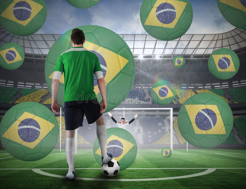 Football player about to take a penalty. Composite image of football player about to take a penalty against football pitch in large stadium stock photo