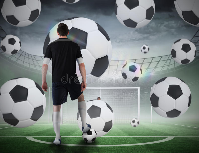 Football player about to take a penalty. Composite image of football player about to take a penalty against football pitch in large stadium royalty free stock photography
