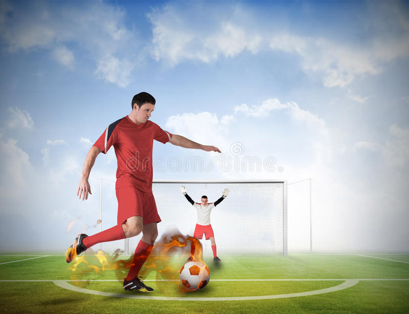 Football player about to take a penalty. Composite image of football player about to take a penalty against football pitch under blue sky stock photography