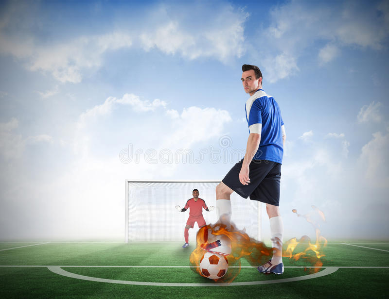 Football player about to take a penalty. Composite image of football player about to take a penalty against football pitch under blue sky stock photo