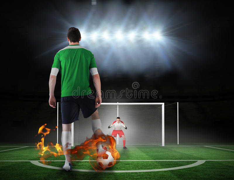 Football player about to take a penalty. Composite image of football player about to take a penalty against football pitch under spotlights royalty free stock image