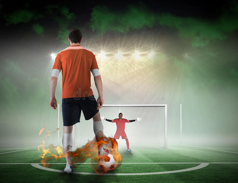 Football player about to take a penalty. Composite image of football player about to take a penalty against football pitch under spotlights stock photo