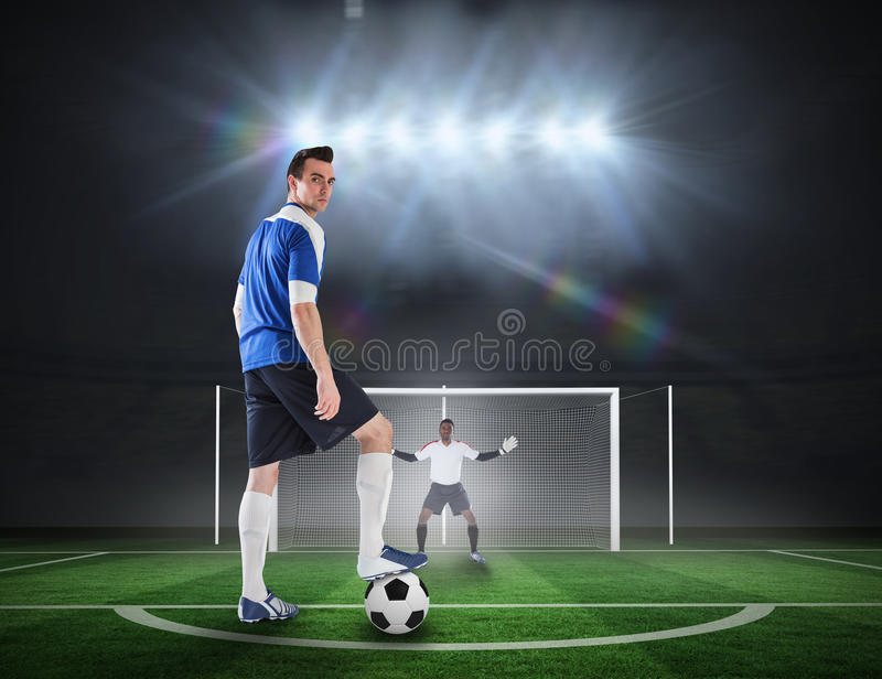 Football player about to take a penalty. Composite image of football player about to take a penalty against football pitch under spotlights stock image