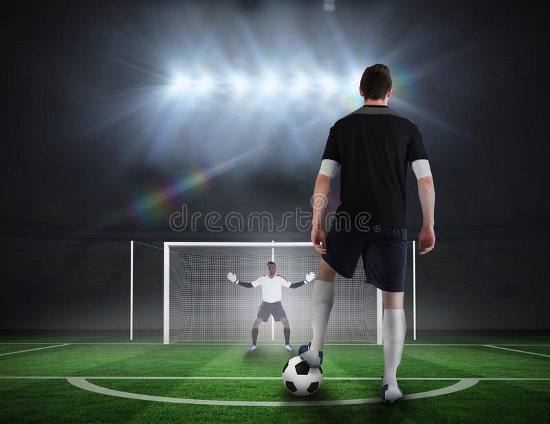 Football player about to take a penalty. Composite image of football player about to take a penalty against football pitch under spotlights royalty free stock photos