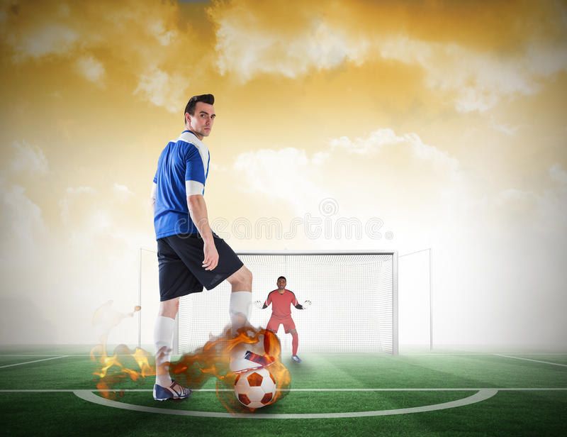 Football player about to take a penalty. Composite image of football player about to take a penalty against football pitch under yellow sky stock image