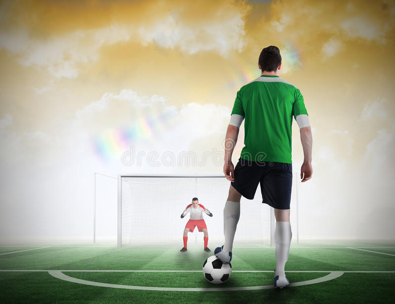Football player about to take a penalty. Composite image of football player about to take a penalty against football pitch under yellow sky royalty free stock images