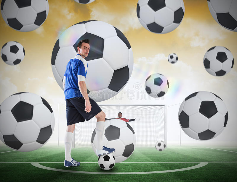 Football player about to take a penalty. Composite image of football player about to take a penalty against football pitch under yellow sky royalty free stock photo