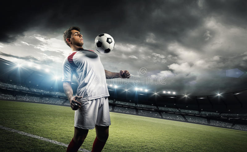Football player withstand a ball with his chest in the stadium. The imaginary stadium is modelled and rendered stock photos