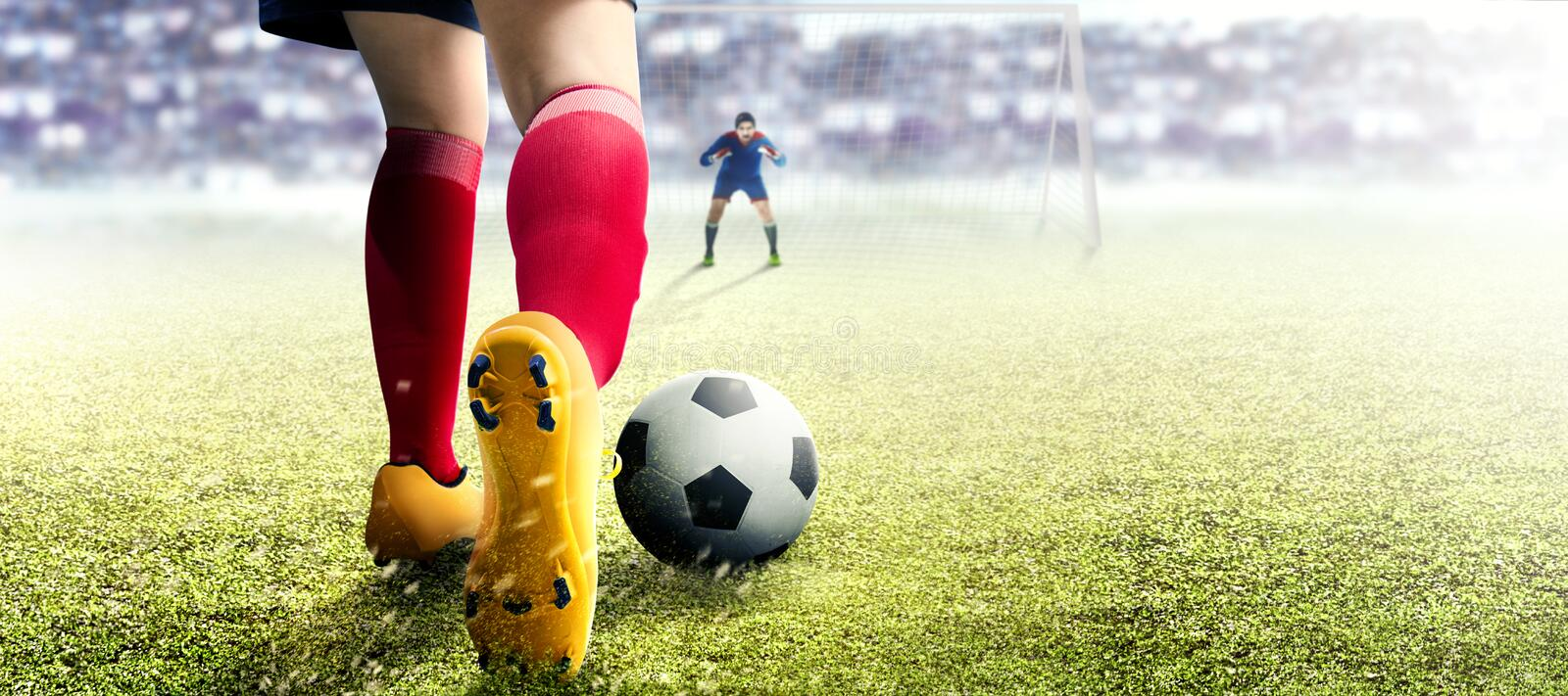 Football player woman in orange jersey kicking the ball in the penalty box. On football field stock photo