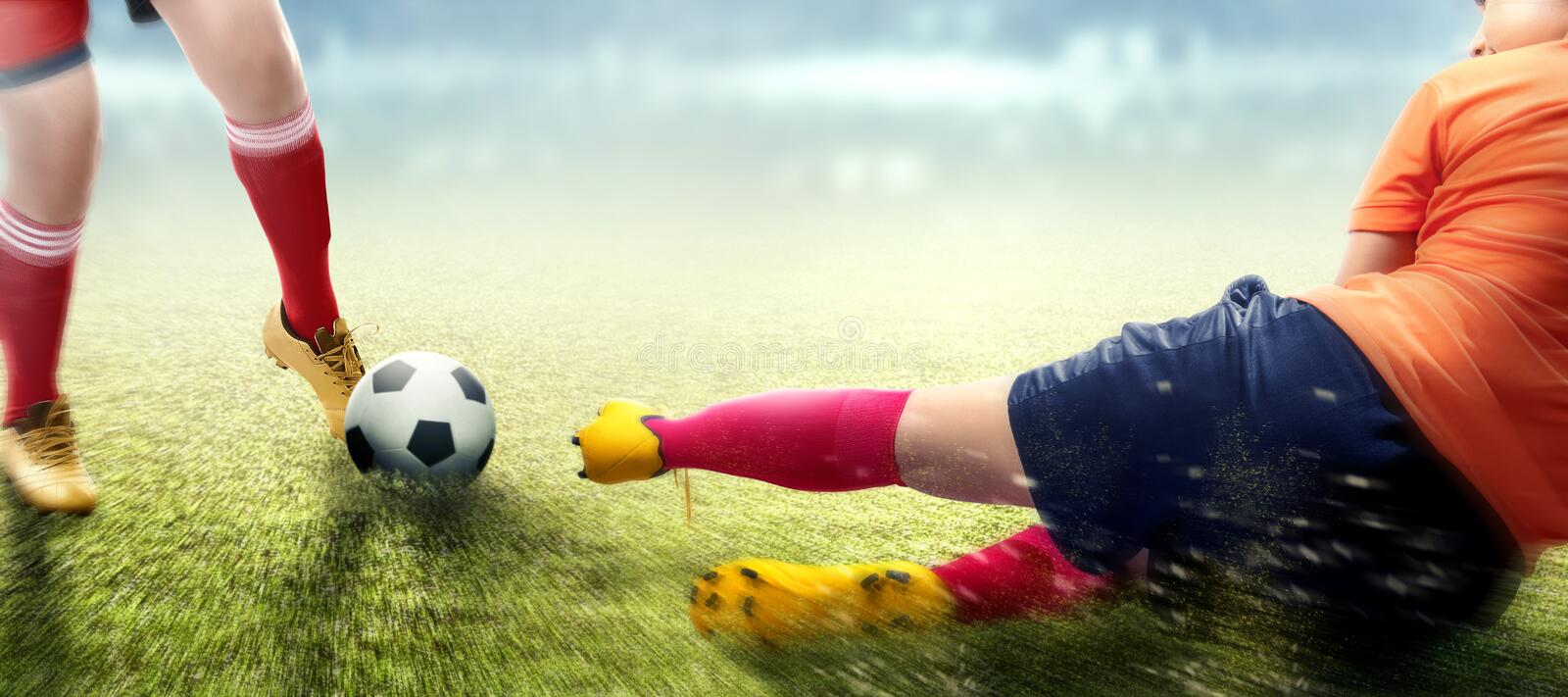 Football player woman in orange jersey sliding tackle the ball from her opponent. On football field stock images