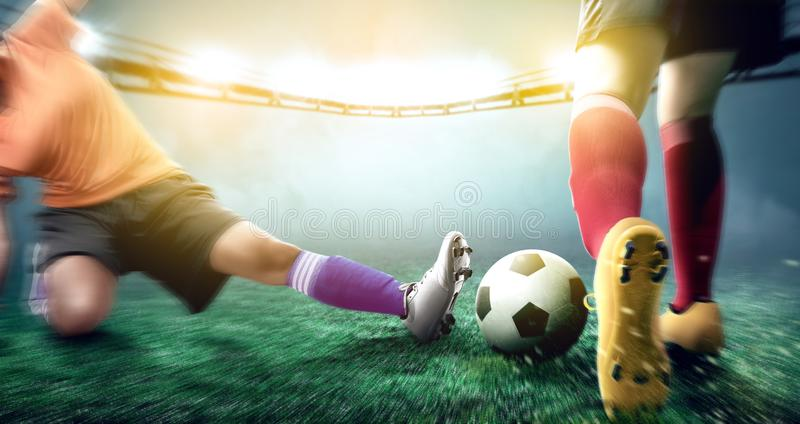 Football player woman in orange jersey sliding tackle the ball from his opponent. On football field at stadium stock photos
