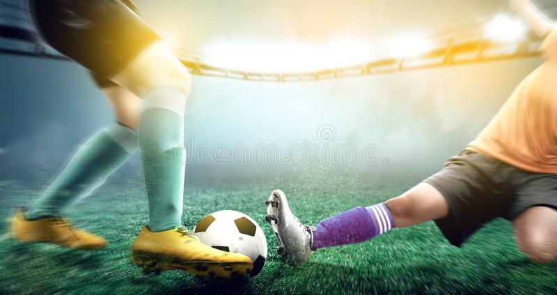 Football player woman in orange jersey sliding tackle the ball from his opponent. On football field at stadium royalty free stock image