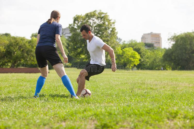 Football player woman sliding tackle the ball from his opponent on football field at stadium. Football player women sliding tackle the ball from his opponent on royalty free stock photography