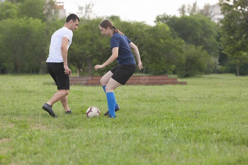 Football player woman tackle the ball from her opponent on football field at stadium. Football player women tackle the ball from her opponent on football field stock photo
