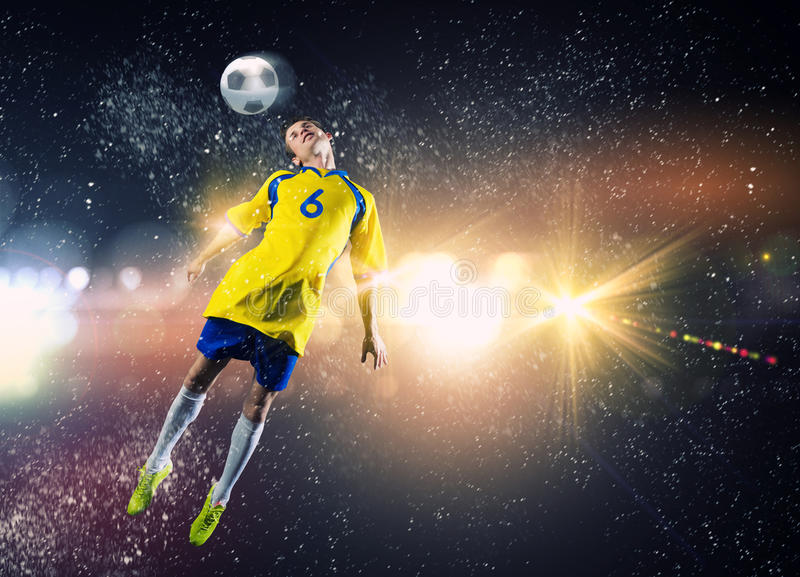 Football player. Young football player on stadium kicking ball with head in jump royalty free stock photography