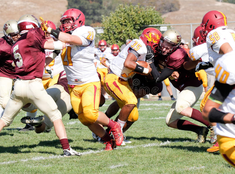 Football Players Colliding During a Game. A football player on the Scotts Valley Falcons hits a player with the ball during a game against the Los Banos Tigers royalty free stock photo