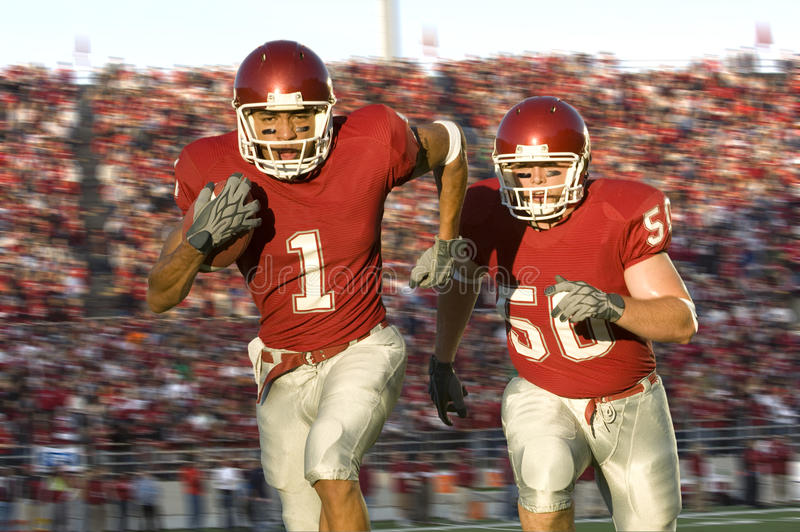 Football Players Running Down the Field royalty free stock photo