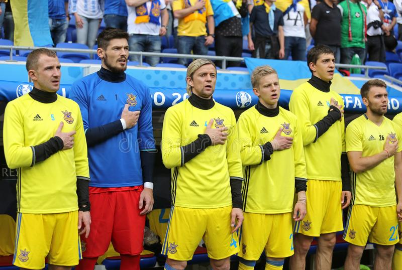 Football players sing the national anthem. LYON, FRANCE - JUNE 16, 2016: Players of Ukraine football team sing the national anthem before UEFA EURO 2016 game stock photography