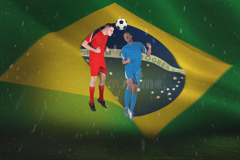 Football players tackling for the ball. Against brazilian flag waving stock photo