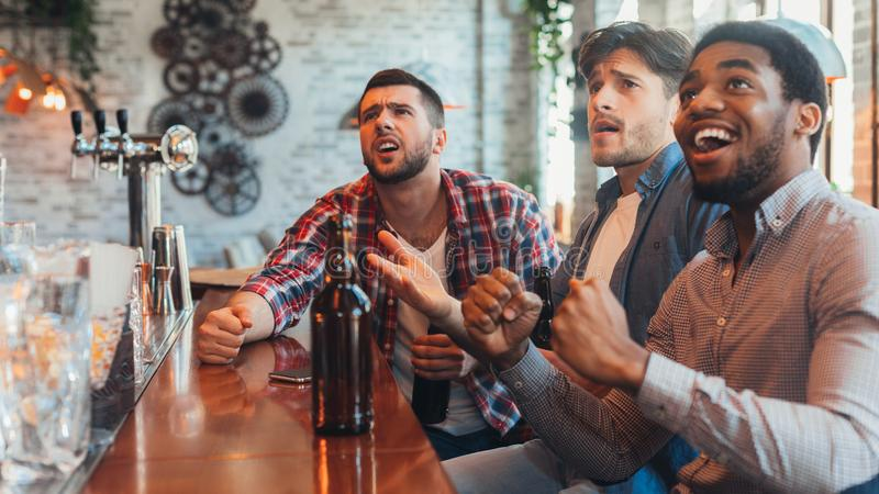 Football in pub. Friends watching match in sport bar. Football in pub. Friends watching match and drinking beer in sport bar stock photos