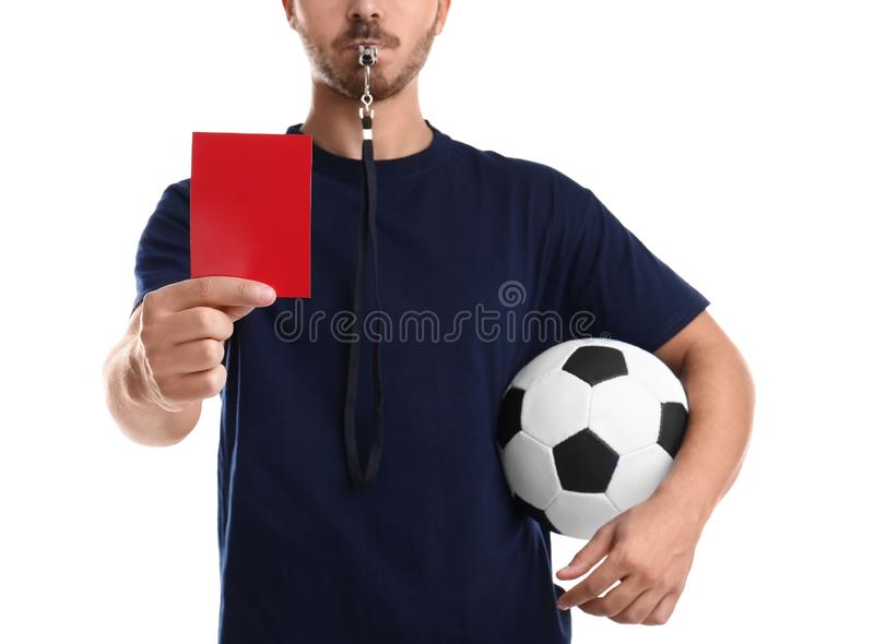 Football referee with ball and whistle holding red card stock image