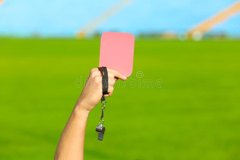 Football referee holding red card and whistle at stadium royalty free stock photography
