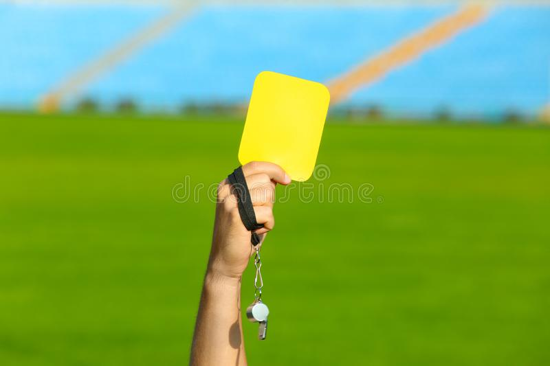 Football referee holding yellow card and whistle at stadium royalty free stock photos