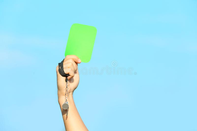 Football referee showing green card against blue sky stock images