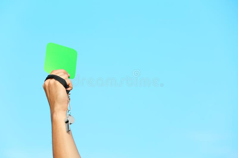 Football referee showing green card against blue sky stock photography