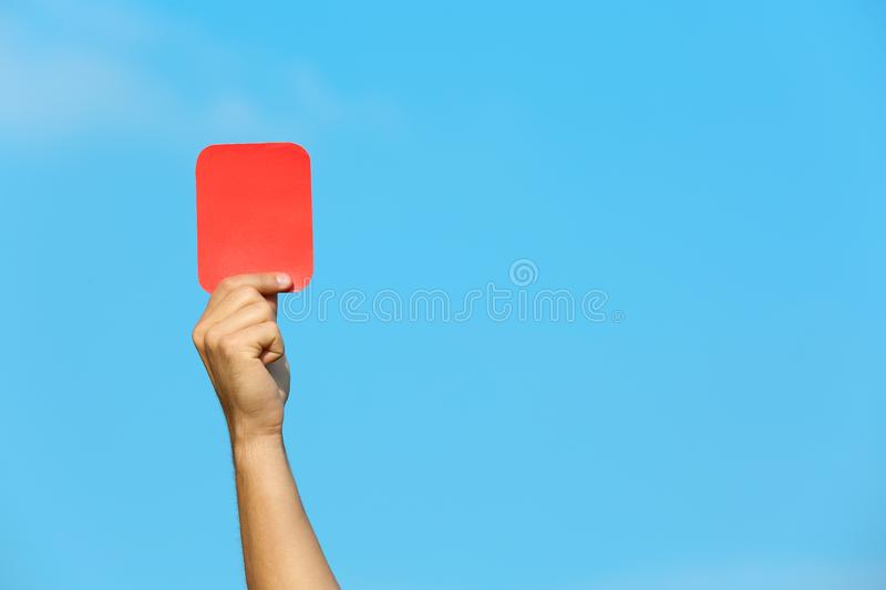 Football referee showing red card against blue sky stock image